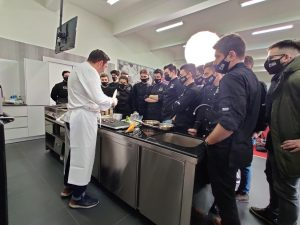 chef lecturer showing the class culinary techniques class gathered around a table in the show kitchen