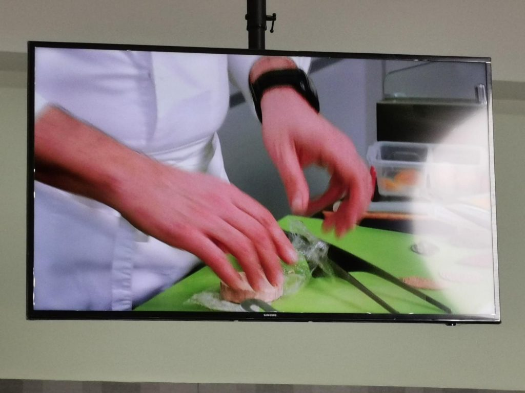 chef working during the webinar displayed on TV screen