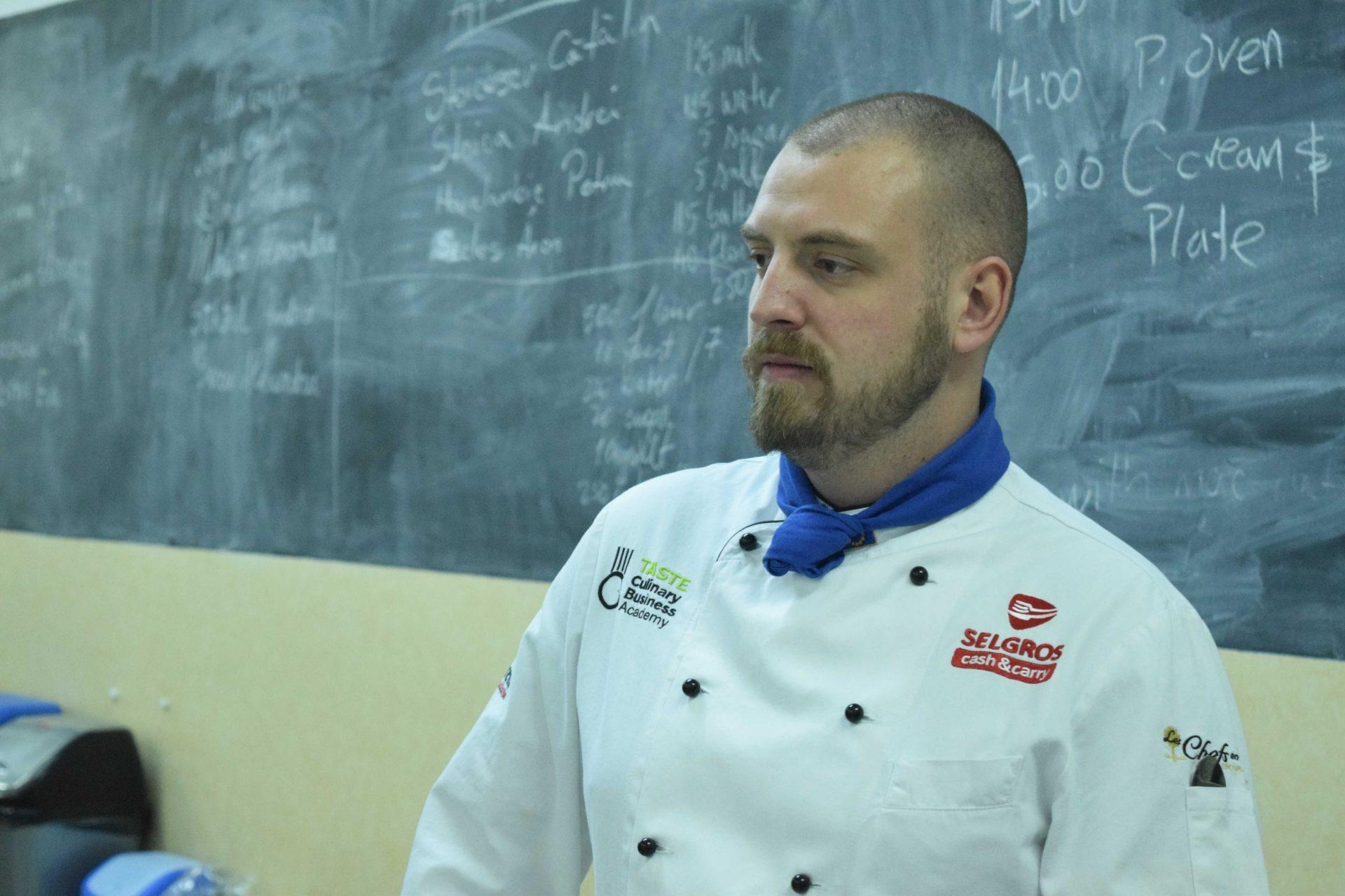 chef jon jordache portrait during class in front of practice kitchen blackboard
